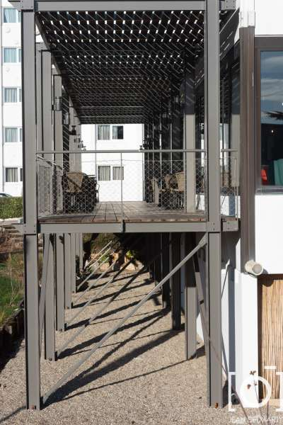 une structure métallique thermolaquée avec platelage en lame bois, claustras et brise soleil en lame bois, ainsi que des garde-corps filet et câble inox à l'Ibis de Chasse sur Rhône