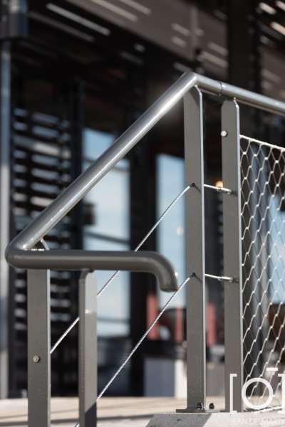 une structure métallique thermolaquée avec platelage en lame bois, claustras et brise soleil en lame bois, ainsi que des garde-corps filet et câble inox à l'Ibis de Chasse sur Rhône, vue d'un barrière