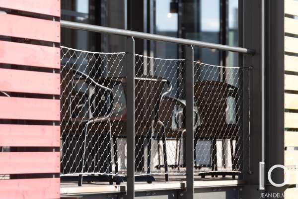 une structure métallique thermolaquée avec platelage en lame bois, claustras et brise soleil en lame bois, ainsi que des garde-corps filet et câble inox