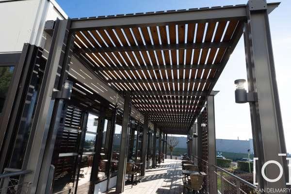 une structure métallique thermolaquée avec platelage en lame bois, claustras et brise soleil en lame bois, ainsi que des garde-corps filet et câble inox vue de gauche